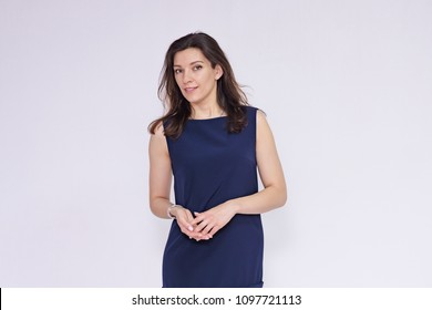 I want to talk with you. portrait of a beautiful brunette girl in a dress on a white background in different poses. She is standing right in front of the camera smiling and looking happy.