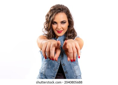 I want you! Close up portrait of a young attractive woman with a jeans outfit pointing the spectator with both hands to join her. Confident and engaging gesture.
