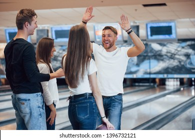 I want your high five. Young cheerful friends have fun in bowling club at their weekends.