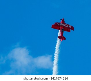 Wantagh, New York, USA - 24 May 2019: The Oracle d bi-plane perfoming on the Friday practice day of Memorial Day weekend at Jones Beach, NY. climbing high into the sky leaving a trail of smoke.