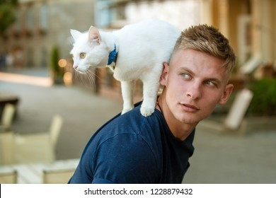Wanting to know about everything. Cat stands on back of his owner. Happy man on walk with cat pet. Muscular man hold cute pedigree cat. Happy cat owner with muscular look.
