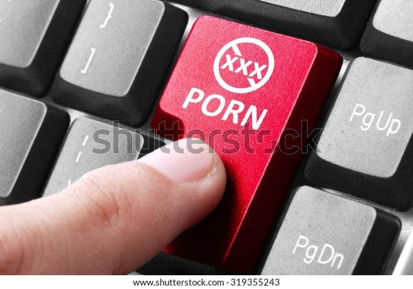 Wanting to watch porn. gesture of finger pressing porn button on a computer keyboard