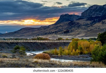 Wapiti Valley sunrise along the Shoshone river in Autumn with the golden aspens along the river and split rail fence in the foreground with orange sunrise through the clouds behind the hills.