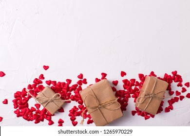 Wapped boxes with presents , little red hearts on white textured background. Place for text.  Flat lay.