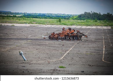 War actions aftermath, Ukraine and Donbass conflict, destroyed tank and artillery rocket stucked in asphalt in former Airport area near city of Donetsk