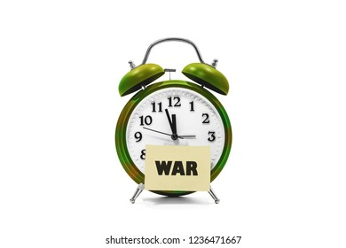 war concept, camouflage color alarm clock with war word on notepad