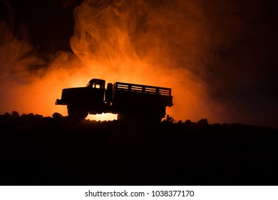 War Concept. Military silhouettes fighting scene on war fog sky background, World War Soldiers Silhouettes Below Cloudy Skyline At night. Attack scene. Armored vehicles. Trucks and army jeep