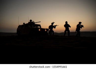 War Concept. Military silhouettes fighting scene on war foggy sky background at sunset. Armored vehicles with soldiers ready to attack. Artwork decoration. Selective focus