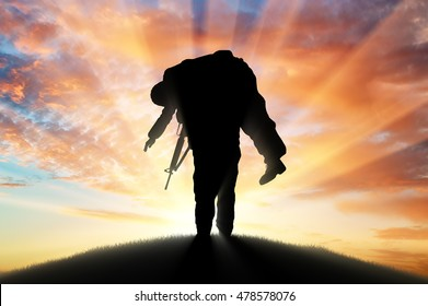 War and conflict concept. Soldier carries a wounded soldier at sunset