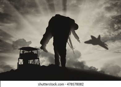 War and conflict concept. Soldier carries a wounded soldier on a background of a watchtower and flying fighter