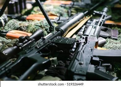 War guns arsenal modern military assault rifles shotgun weapon arms outdoors on natural background