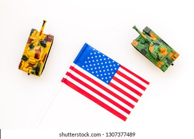 War, military threat, military power concept. USA. Tanks toy near american flag on white background top view