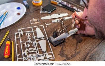 War plane toy model building or construction, handcraft on table with different materials.