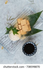 Warabimochi is a jelly-like confection made from bracken starch and covered or dipped in kinako (sweet toasted soybean flour) served with vanilla ice cream and maple syrup in glass plate on washi.