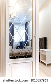 Wardrobe in the bedroom with a mirror smooth and with a bevel. Interior with contrast of light and dark