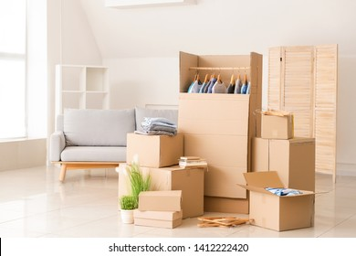 Wardrobe boxes with clothes and other things prepared for house moving in room