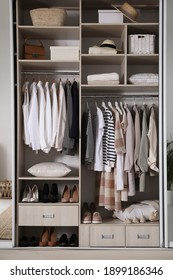 Wardrobe closet with different stylish clothes, shoes and home stuff in room