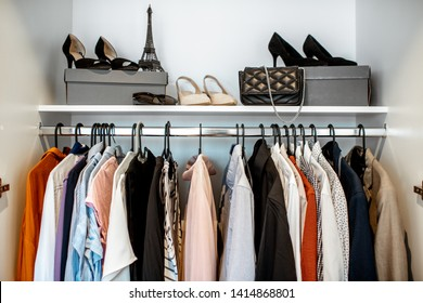 Wardrobe closet full of different clothes and female shoes indoors