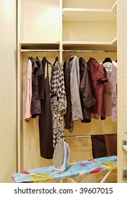 Wardrobe with clothes and ironing board