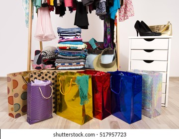 Wardrobe with clothes and shopping bags, on line shopping. Close up on many full bags in a woman closet.