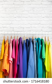 Wardrobe of women's clothing blouses and shirts hang on hangers in the order of colors of the rainbow on the background of brick wall. Concept of stylish women's wardrobe. Advertising space