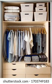 Wardrobe with perfect order clothes in blue and light shades on the hangers and things in containers. The concept of organizers and cleanliness in the house