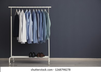 Wardrobe rack with men's clothes near grey wall. Space for text