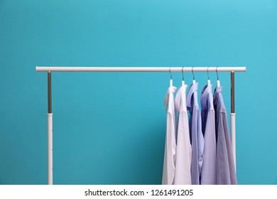 Wardrobe rack with men's clothes on color background. Space for text