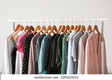 Wardrobe rack with stylish clothes near white wall indoors