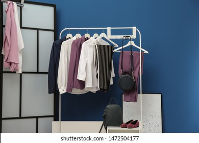 Wardrobe rack with women's clothes and shoes at blue wall in room