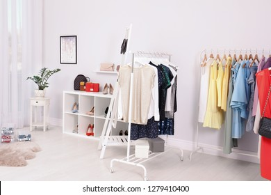 Wardrobe racks with different stylish clothes in light room