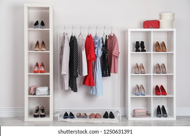 Wardrobe shelves with different stylish shoes and clothes indoors. Idea for interior design