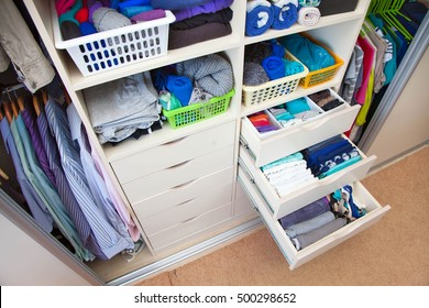 Wardrobe with women's and men's clothing. Drawers with underwear, socks and shirts.
