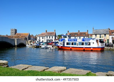WAREHAM, UNITED KINGDOM - JULY 19, 2016 - Boats moored on the river with views towards the bridge and town, Wareham, Dorset, England, UK, Western Europe, July 19, 2016.