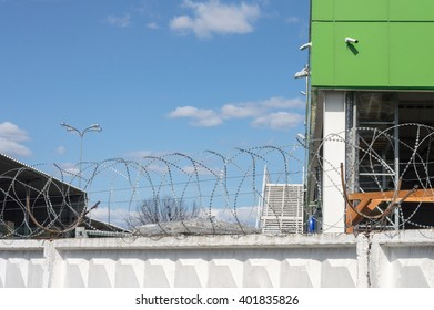 Warehouse behind the fence with barbed wire