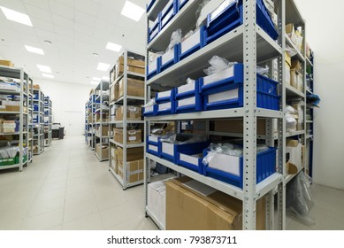 Warehouse of components for the electronics industry. White metal racks with blue plastic trays and cardboard boxes installed in them.