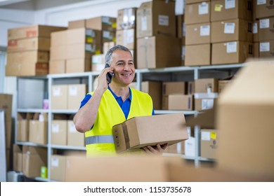 Warehouse delivery check. Factory worker. Smiling warehouse workers preparing a shipment in a large warehouse. Warehouse worker checking goods .