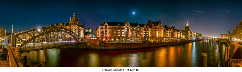 """The Warehouse District (Speicherstadt) in Hamburg, Germany, at night. The panoramic view is across the inner harbor (Binnenhafen) with the bridge """"Brooksbrücke""""."""