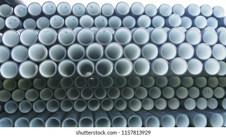 Warehouse of finished plastic pipes industrial outdoors storage site. Manufacture of plastic water pipes factory. Process of making plastic tubes on the machine tool with the use of water and air