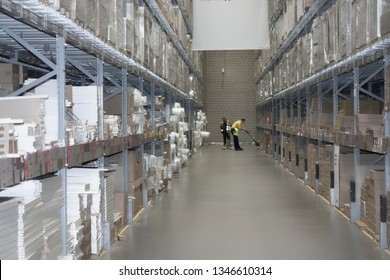 Warehouse furniture store. Huge shelves with pallets and furniture products. Two warehouse staff unload goods