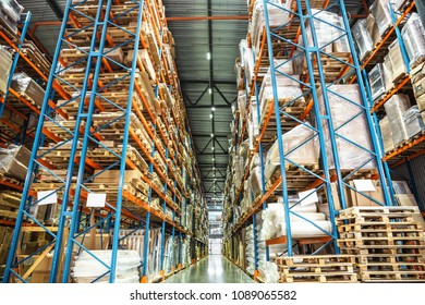 Warehouse or hangar storage racks or shelves with boxes and goods. Industrial logistic delivery and distribution concept