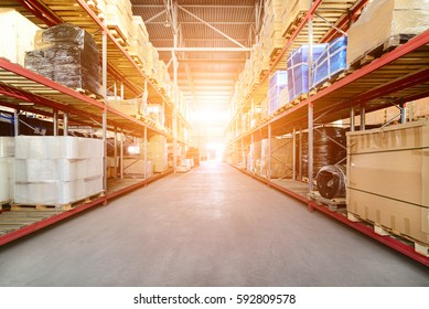 Warehouse industrial and logistics companies. Commercial warehouse. Boxes and crates stocked on the shelves of three storey. Bright sunlight.