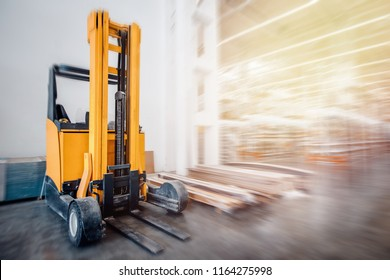 Warehouse industrial premises for storing materials and wood, there is forklift containers. Concept logistics, transport. Motion blur effect. Bright sunlight.