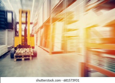Warehouse industrial premises for storing materials and wood, there is a forklift for containers. Concept logistics, transport. Motion blur effect. Bright sunlight.