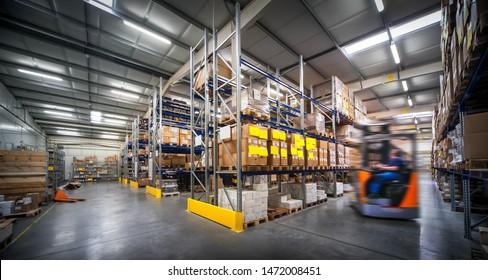 Lagerinnerer mit unscharfem Gabelstapler und Mitarbeiter im Logistikzentrum