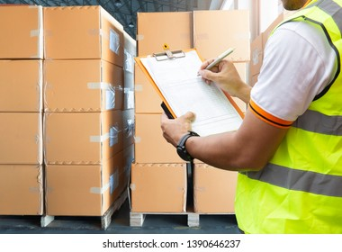 Warehouse inventory management. courier shipment transportation. Stack of cardboard boxes on wooden pallet.  warehouse worker is writing on clipboard with inspecting the shipment.