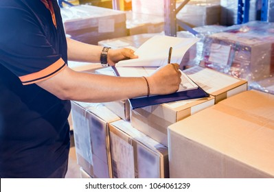 Warehouse inventory management. Warehouse worker is writing on clipboard with checking inventory of products in warehouse factory.