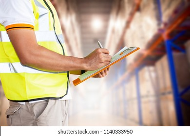 Warehouse inventory management. Young man worker writing on clipboard inspecting the products on tall shelves storage warehouse.