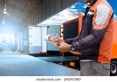 Warehouse Logistics and transportation, Worker holding clipboard is control loading cargo courier shipment, truck docking at warehouse