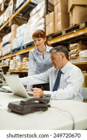 Warehouse management talking and looking at laptop in a large warehouse